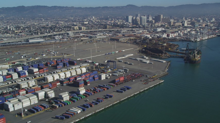 5K stock footage aerial video Flyby cargo cranes, containers, cargo ships at Port of Oakland, Downtown Oakland in the background, California Aerial Stock Footage | DCSF05_079