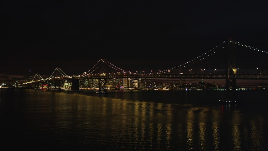 5K stock footage aerial video Low altitude approach to the Bay Bridge and downtown skyline, San Francisco, California, night Aerial Stock Footage | DCSF06_001
