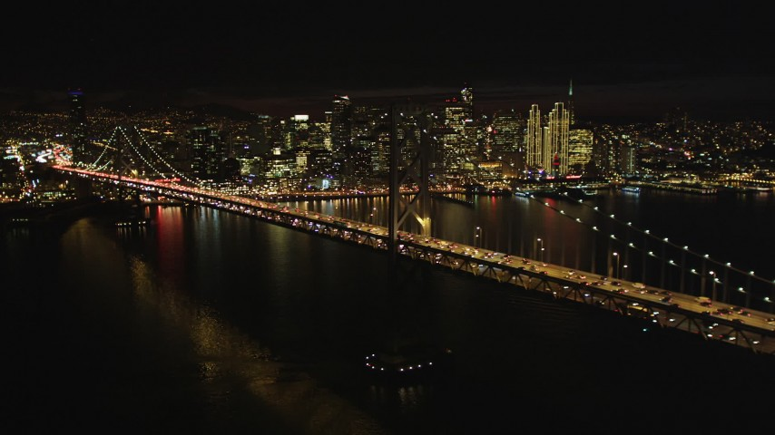5K stock footage aerial video Flying by Bay Bridge with the downtown skyline behind it, San Francisco, California, night Aerial Stock Footage | DCSF06_014