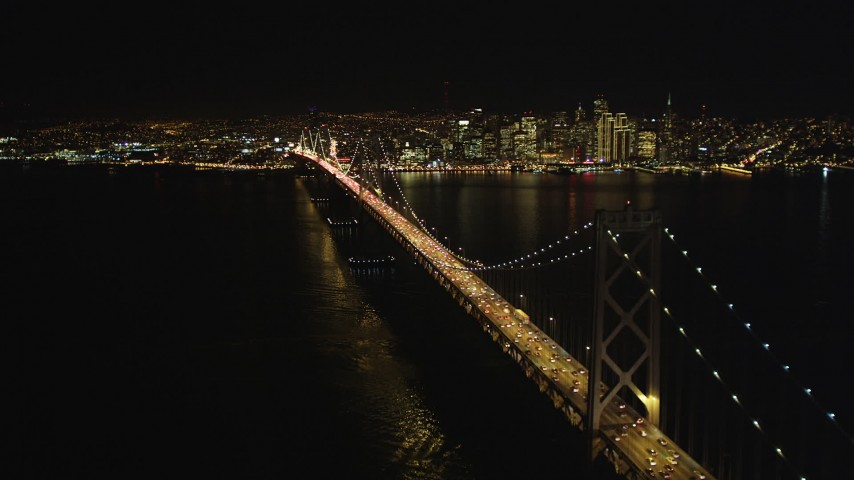 5K stock footage aerial video Approach heavy traffic on the upper deck of the Bay Bridge, Downtown San Francisco skyline in background, California, night Aerial Stock Footage | DCSF06_032
