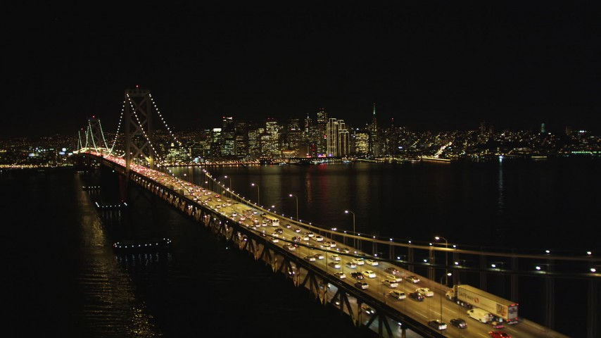5K stock footage aerial video Flying by heavy Bay Bridge traffic, Downtown San Francisco skyline in background, California, night Aerial Stock Footage | DCSF06_033