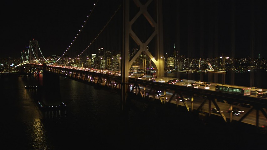 5K stock footage aerial video Flying by Bay Bridge, San Francisco skyline in the background, California, night Aerial Stock Footage DCSF06_034 | Axiom Images