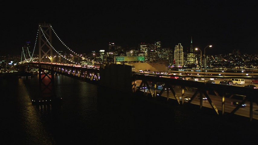 5K stock footage aerial video Flying by Bay Bridge, focus on San Francisco skyline, California, night Aerial Stock Footage | DCSF06_035
