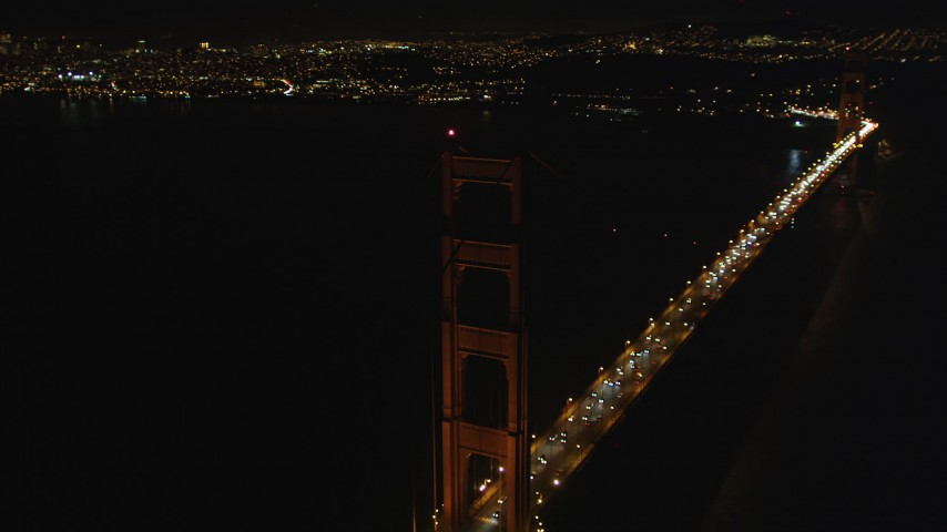Tilt from light traffic to tower of Golden Gate Bridge, San Francisco, California, night Aerial Stock Footage | DCSF06_043