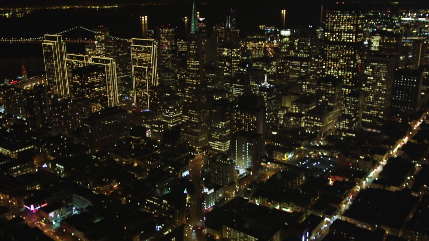 5K stock footage aerial video Tilt up Columbus Avenue to reveal Transamerica Pyramid and skyscrapers, Downtown San Francisco, California, night Aerial Stock Footage | DCSF06_065