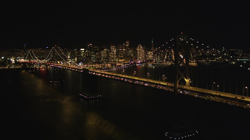 5K stock footage aerial video Flying away from the Bay Bridge, skyline in the background, San Francisco, California, night Aerial Stock Footage DCSF06_087 | Axiom Images