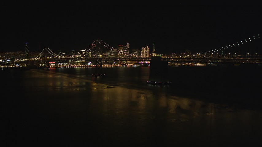 5K stock footage aerial video Fly away from Bay Bridge and the downtown skyline, San Francisco, California, night Aerial Stock Footage | DCSF06_088