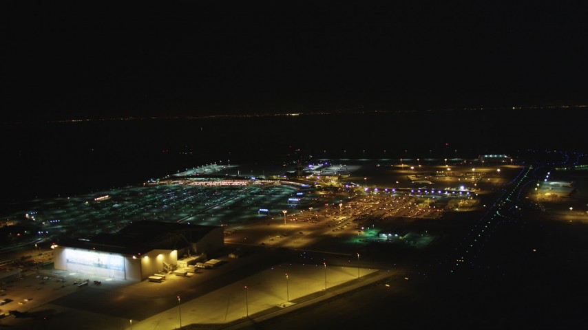 5K stock footage aerial video Track a civilian plane as it lands at Oakland International Airport, Oakland, California, night Aerial Stock Footage | DCSF06_103