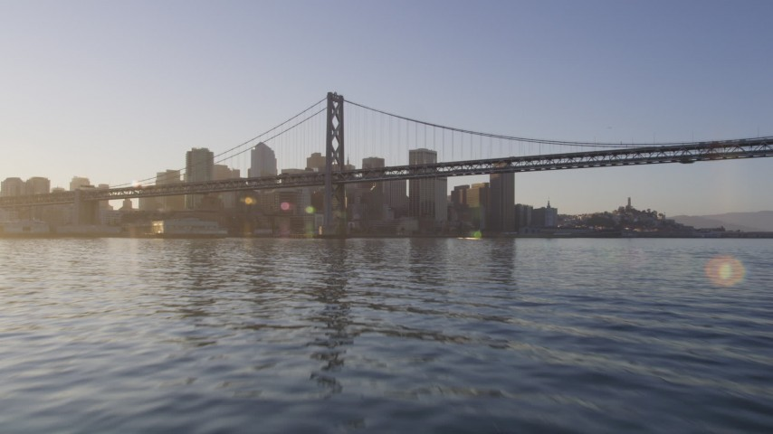 5K stock footage aerial video Fly low over the bay to approach Bay Bridge, Downtown San Francisco, California, sunset Aerial Stock Footage | DCSF07_002