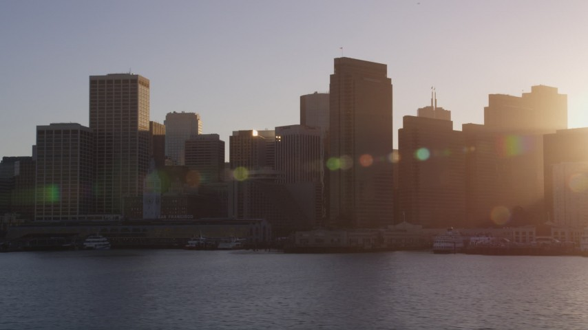 5K stock footage aerial video Fly low past the Ferry Building and skyline of Downtown San Francisco, California, sunset Aerial Stock Footage | DCSF07_013