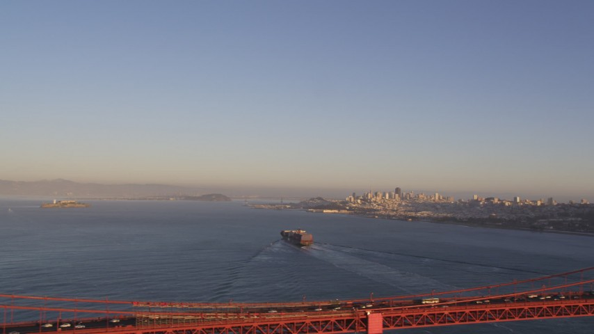 5K stock footage aerial video Cargo ship sailing the bay, Golden Gate Bridge, skyline in the distance, San Francisco, California, sunset Aerial Stock Footage | DCSF07_038