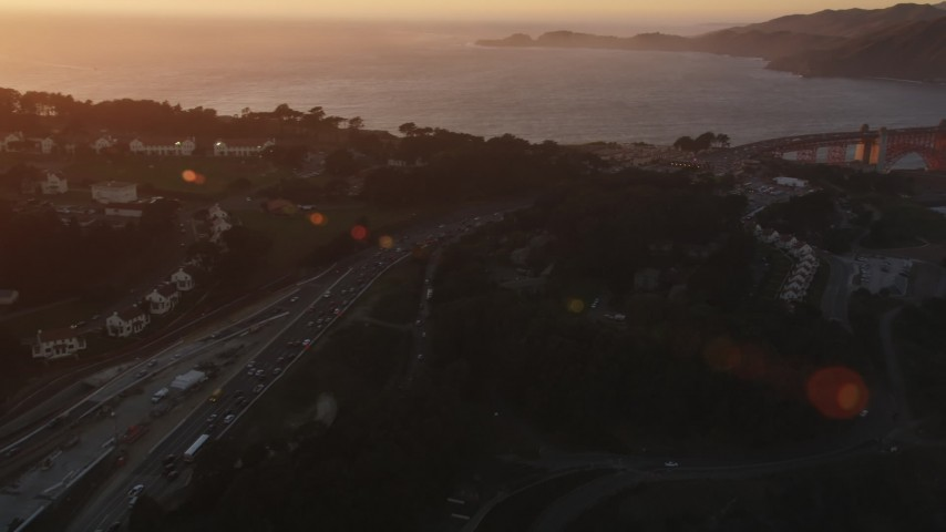 5K stock footage aerial video Pan across Highway 101 in Presidio, reveal Golden Gate Bridge, San Francisco, California, sunset Aerial Stock Footage | DCSF07_051