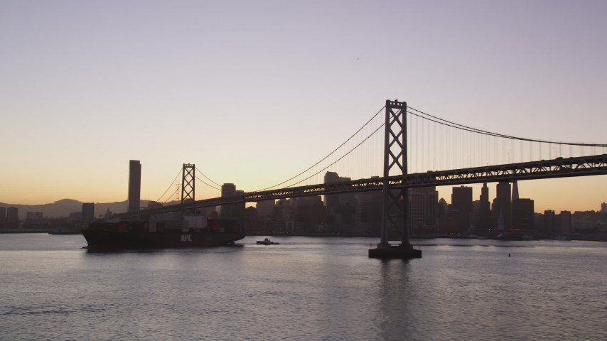 5K Aerial Video Flying away from cargo ship sailing under the Bay Bridge, San Francisco, California, twilight Aerial Stock Footage DCSF07_069 | Axiom Images