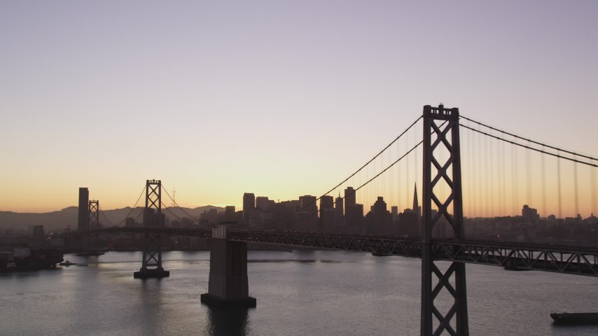 5K Aerial Video Flyby Bay Bridge with a view of Downtown San Francisco, California, twilight Aerial Stock Footage | DCSF07_070