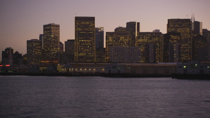 5K Aerial Video Fly low by piers and approach skyline of Downtown San Francisco, California, twilight Aerial Stock Footage | DCSF07_087