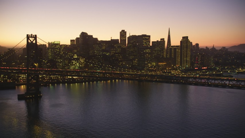 5K Aerial Video Flying by the Bay Bridge, skyline in the background, Downtown San Francisco, California, twilight Aerial Stock Footage | DCSF07_098