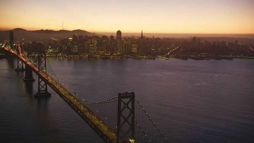 5K Aerial Video Reverse view of heavy Bay Bridge traffic and Downtown San Francisco, California, twilight Aerial Stock Footage | DCSF07_100