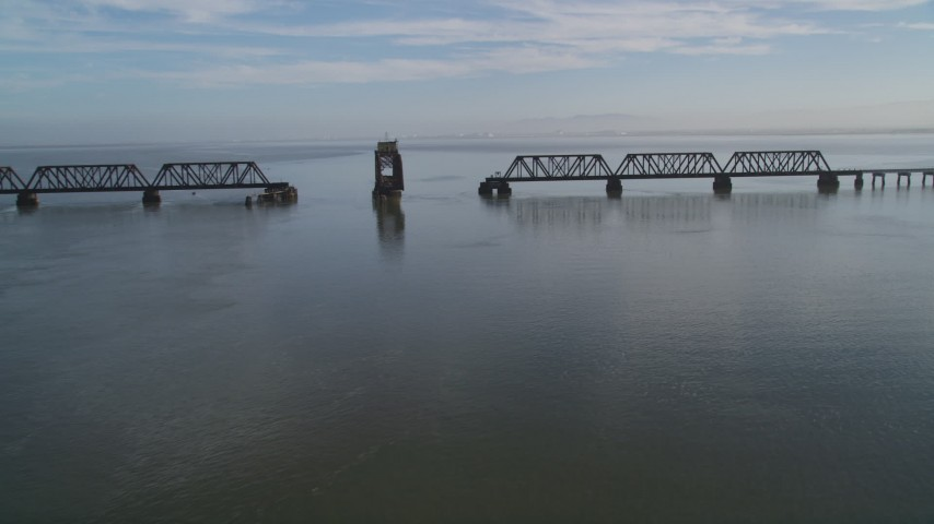 5K Aerial Video Tilt from the bay to reveal and flyby the Dumbarton Rail Bridge in San Francisco Bay, California Aerial Stock Footage | DCSF09_026