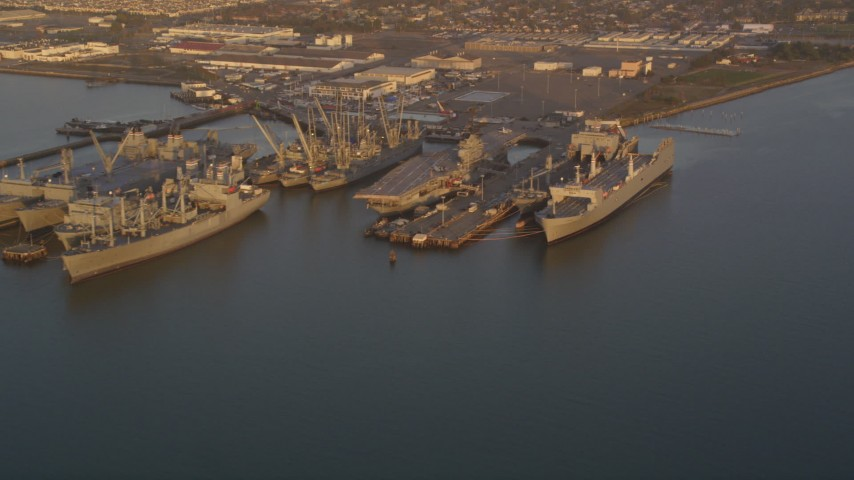 5K Aerial Video Flyby base and reveal USS Hornet and ships at Naval Air Station Alameda, California, sunset Aerial Stock Footage | DCSF10_001