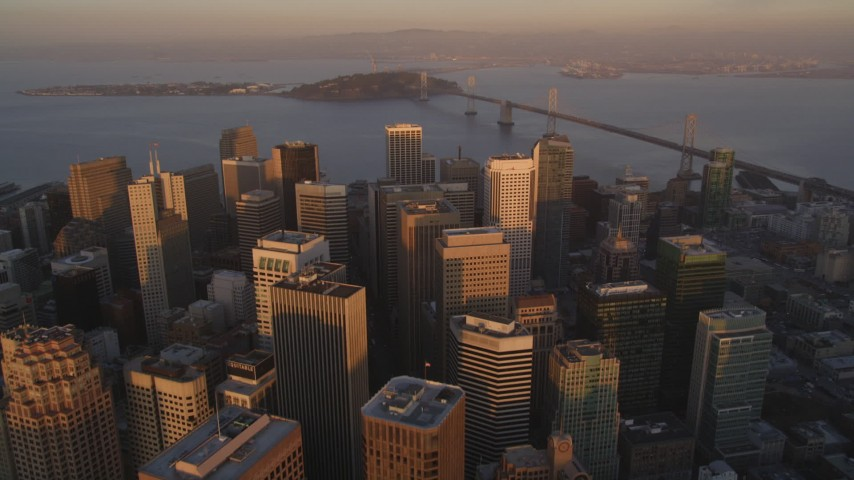 5K Aerial Video Tilt to reveal and fly over skyscrapers in Downtown San Francisco, California, and approach the Bay Bridge, twilight Aerial Stock Footage | DCSF10_006