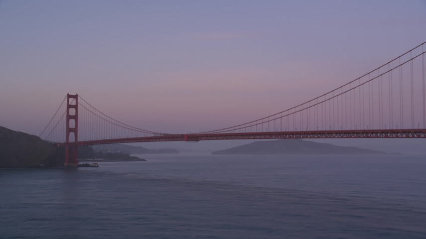 5K Aerial Video Fly low by the Golden Gate Bridge and pan across the span, San Francisco, California, twilight Aerial Stock Footage | DCSF10_030