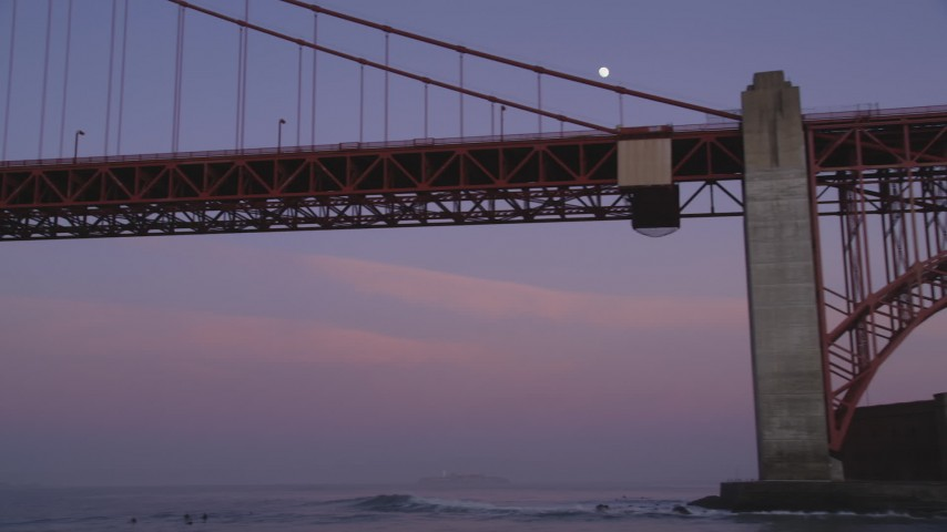 5K Aerial Video of The moon above Presidio cliffs, reveal the Golden Gate Bridge, San Francisco, California, twilight Aerial Stock Footage | DCSF10_032