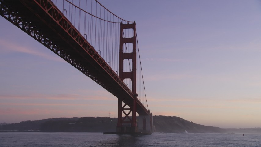 5K Aerial Video Fly low and tilt up to a tower of the Golden Gate Bridge, San Francisco, California, twilight Aerial Stock Footage | DCSF10_035