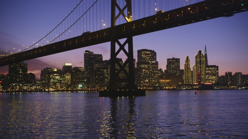5K Aerial Video Fly low beneath Bay Bridge with a view of the Downtown San Francisco skyline, California, twilight Aerial Stock Footage | DCSF10_065