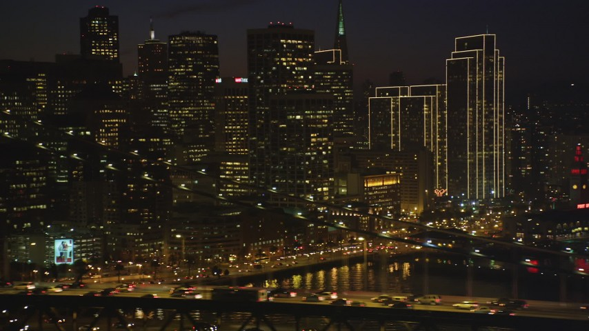 5K Aerial Video of Downtown San Francisco skyscrapers seen while flying by the Bay Bridge, California, night Aerial Stock Footage | DCSF10_082