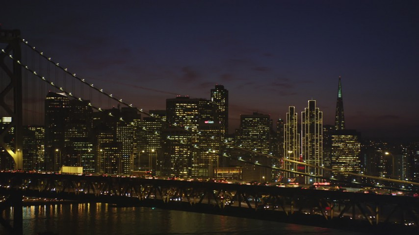 5K Aerial Video of Downtown San Francisco skyline seen while passing by the Bay Bridge, California, night Aerial Stock Footage | DCSF10_083