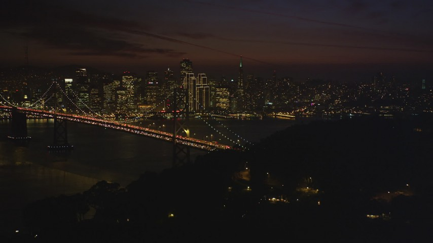 5K Aerial Video of Downtown San Francisco skyline behind the Bay Bridge, seen from Yerba Buena Island, California, night Aerial Stock Footage | DCSF10_086
