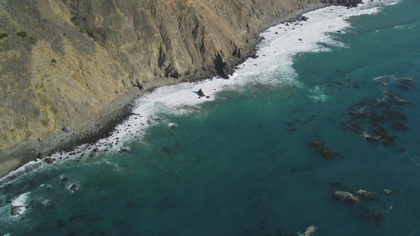 5K Aerial Video Bird's eye view of kelp near waves rolling toward coastal cliffs, Big Sur, California Aerial Stock Footage | DCSF11_033
