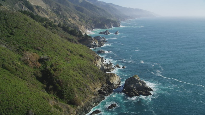 5K Aerial Video Fly over coastal cliffs and tilt to waves crashing into rocks, Big Sur, California Aerial Stock Footage DCSF11_036