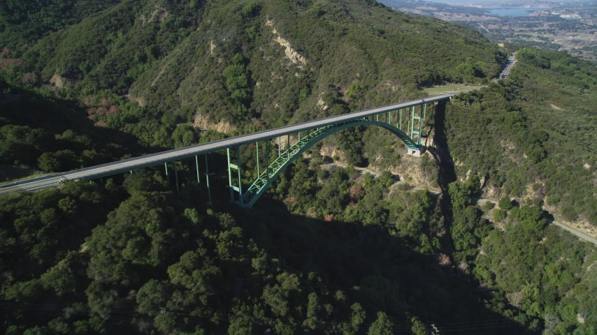5K stock footage aerial video tilt from trees to reveal Cold Springs Canyon Arch Bridge, Santa Ynez Mountains, California Aerial Stock Footage | DFKSF01_047