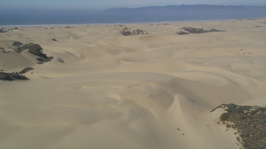 5K stock footage aerial video of approaching sand dunes, ATV riders, Pismo Dunes, California Aerial Stock Footage | DFKSF02_019