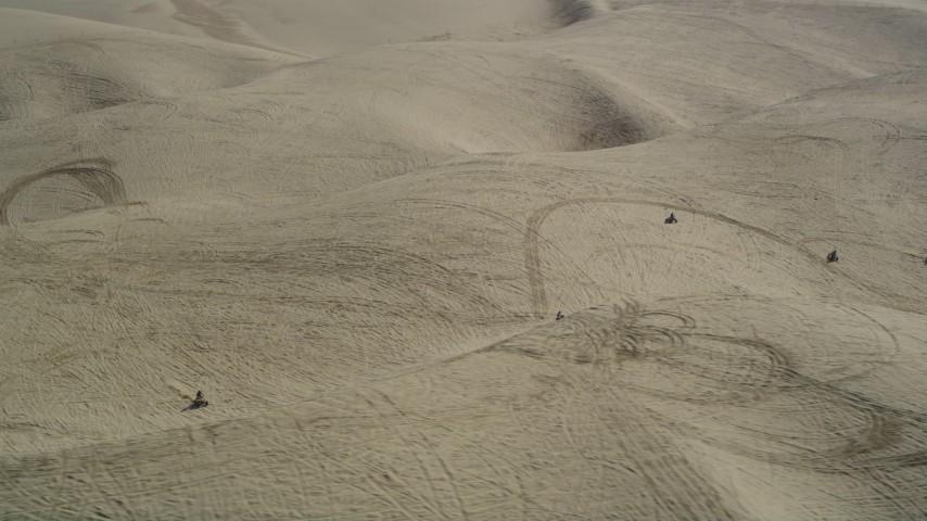 5K stock footage aerial video of orbiting ATV riders cruising over the sand dunes, Pismo Dunes, California Aerial Stock Footage | DFKSF02_021