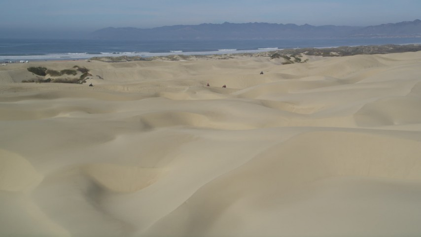 5K stock footage aerial video of panning across sand dunes, revealing ATV riders, Pismo Dunes, California Aerial Stock Footage | DFKSF02_027