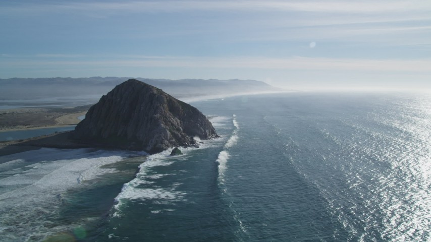 5K stock footage aerial video of flying over waves crashing into Morro Rock, coast, Morro Bay, California Aerial Stock Footage | DFKSF03_013