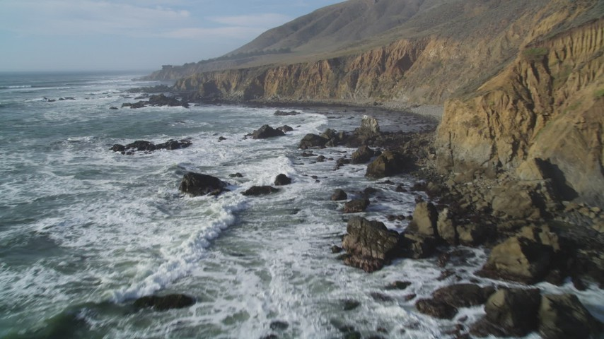 5K stock footage aerial video of flying by the rugged coastal cliffs and over waves, Cambria, California Aerial Stock Footage | DFKSF03_033