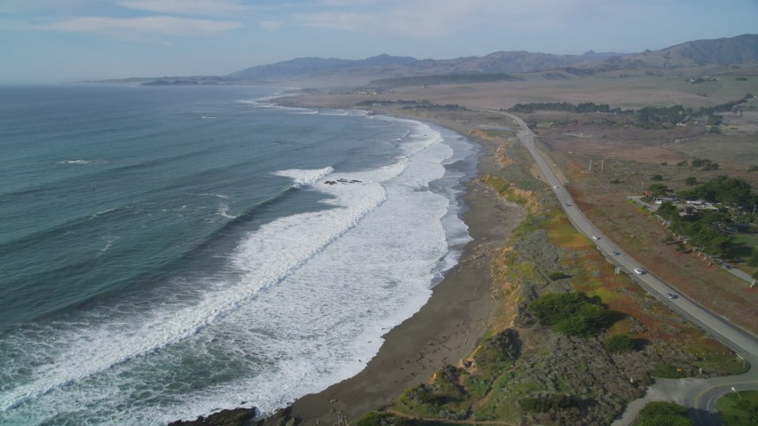 5K stock footage aerial video of flying by Highway 1 as waves roll toward the coast, Cambria, California Aerial Stock Footage | DFKSF03_046