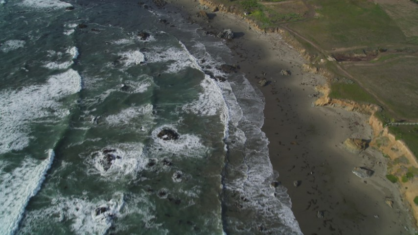 5K stock footage aerial video tilt from ocean to reveal isolated beachfront mansion, Cambria, California Aerial Stock Footage | DFKSF03_048