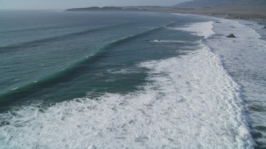 5K stock footage aerial video of flying over ocean waves rolling into the coast, San Simeon, California Aerial Stock Footage | DFKSF03_051