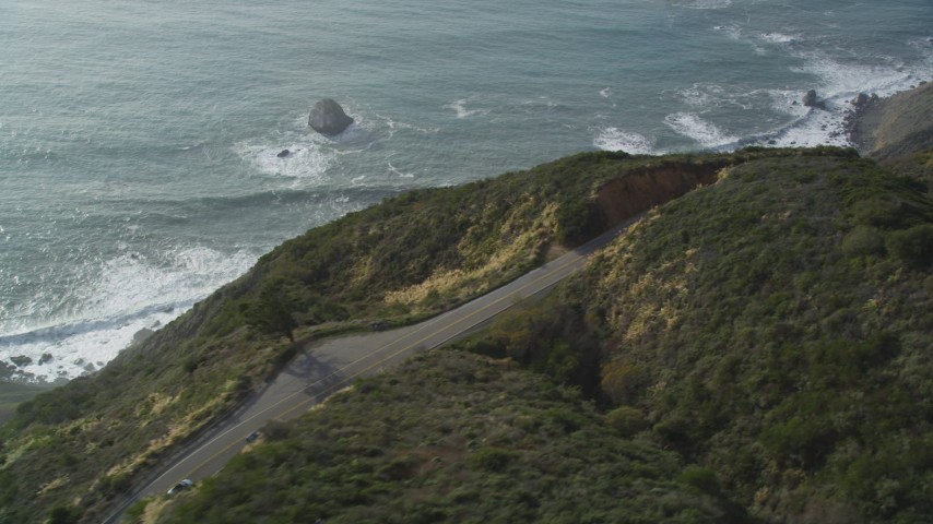 5K aerial video track white convertible on Highway 1, above coastal cliffs, Big Sur, California Aerial Stock Footage | DFKSF03_087