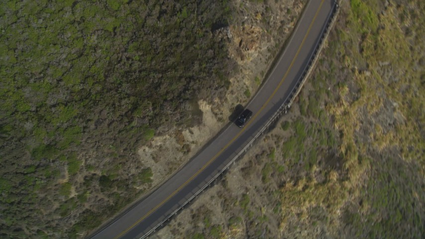 5K aerial video of tracking a black SUV on Highway 1, above coastal cliffs, Big Sur, California Aerial Stock Footage | DFKSF03_088