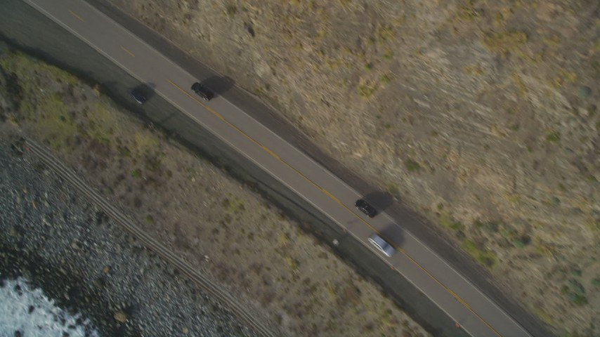 5K aerial video of a bird's eye view of black cars on Highway 1, above coastal cliffs, Big Sur, California Aerial Stock Footage | DFKSF03_090