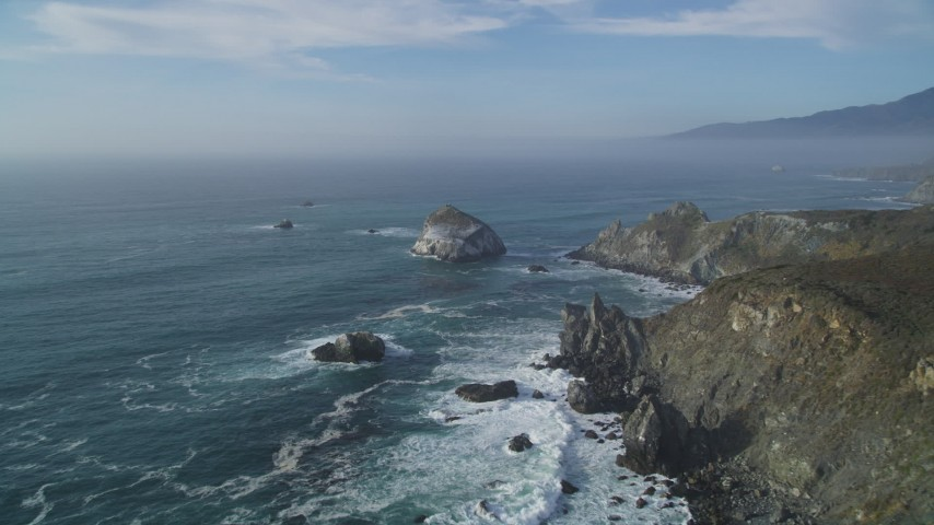 5K aerial video of an approach to a large rock formation off the coast, Big Sur, California Aerial Stock Footage | DFKSF03_093