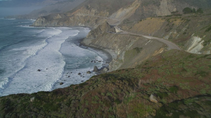 5K stock footage aerial video fly over cliffs, revealing Highway 1 coastal road, Big Sur, California Aerial Stock Footage | DFKSF03_097