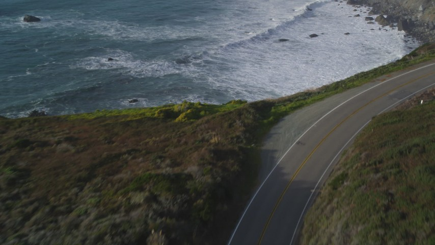 5K aerial video of flying over Highway 1 coastal road, and tilt to ocean waves, Big Sur, California Aerial Stock Footage | DFKSF03_098