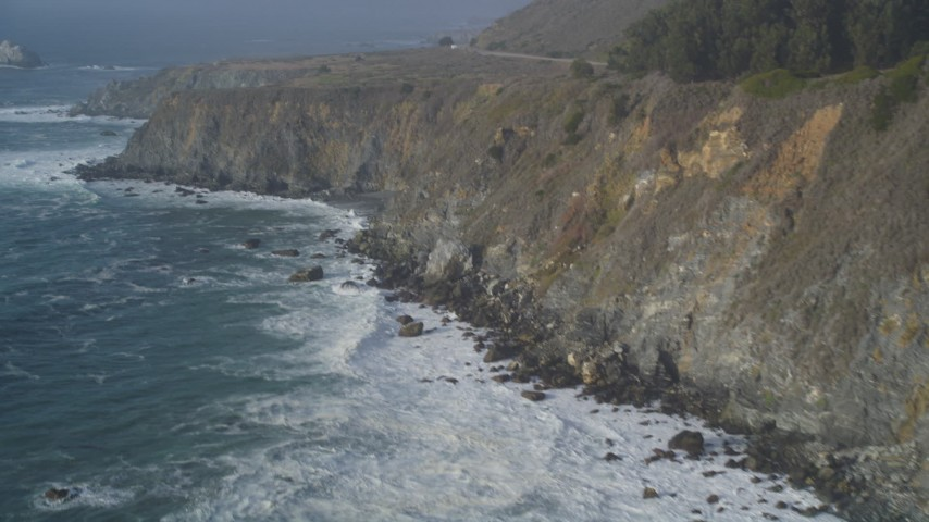 5K stock footage aerial video of tilting from crashing waves to coastal cliffs, Big Sur, California Aerial Stock Footage | DFKSF03_099