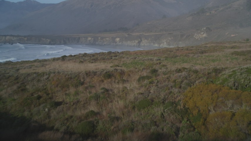5K aerial video fly over coastal cliff, approach ocean waves, Big Sur, California Aerial Stock Footage | DFKSF03_101